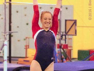 smiling gymnast presenting to judges