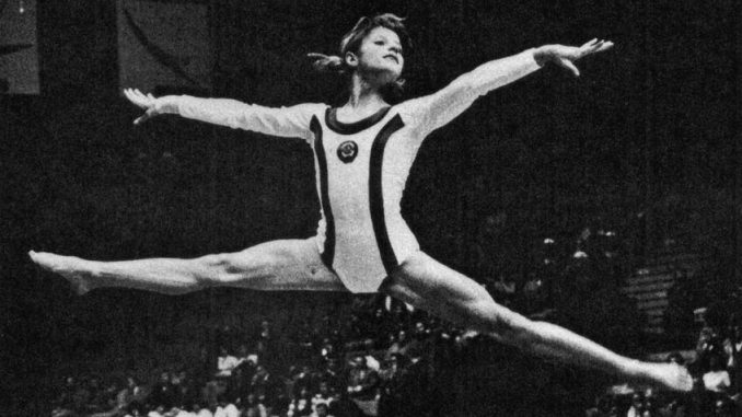 photo of gymnast Olga Korbut doing straddle leap on floor exercise