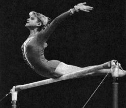 Olga Korbut balanced on the top bar